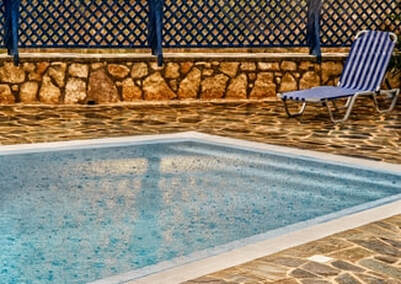 Picture of a view over a pool. In the picture you see a pool deck made out of stone, a part of the pool, a fence and one sunbathing chair.