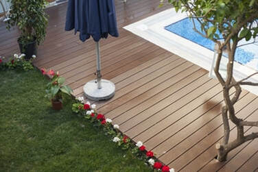 Picture of a wooden pool deck. The border of the swimming pool, a patch of grass, a tree, a flower pot and a umbrella are as well disposed in the picture.